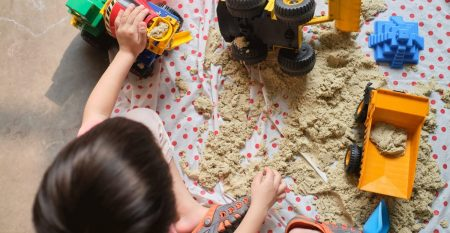 Bird eye view of toddler boy playing with kinetic sand at home,