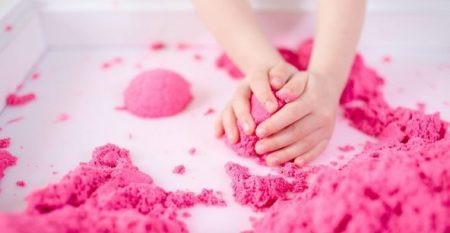 Pink magic sand in a kids hands on a white background close up. Early sensory education. Preparing for School. Development